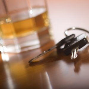 A set of car keys in the foreground and a glass of whiskey behind.