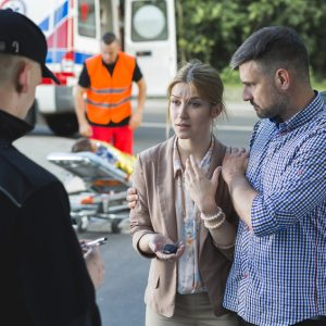 Bystanders describing the scene of an accident to the police officer