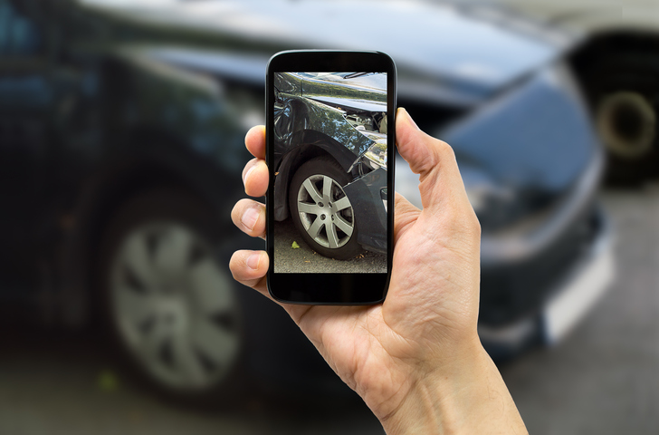 Man photographing his vehicle damages for accident insurance