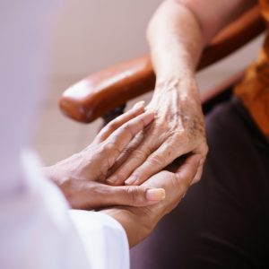 doctor comforts elderly woman in nursing home